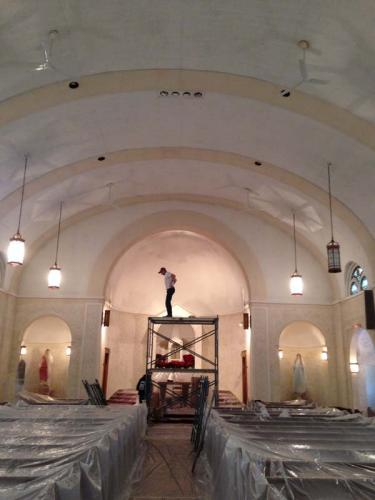 A Braendel team member stands on scaffolding, surveying the work, as other crew members continue to restore this historical church.
