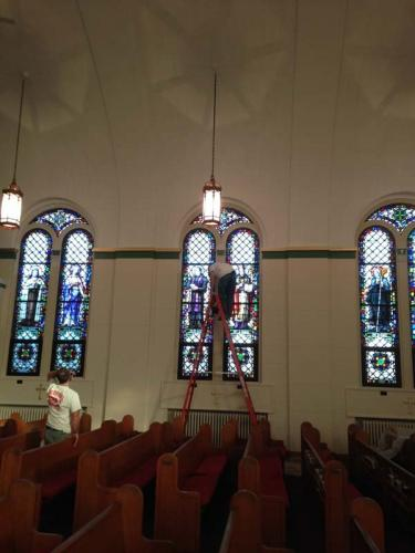 Team members restore the stained glass windows in a historical church.