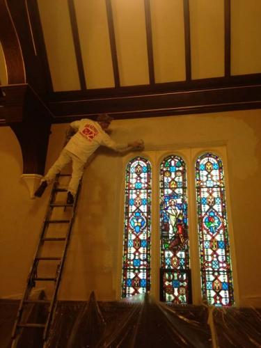 A Braendel team member restores stained glass windows and the wall around them in a historical church.