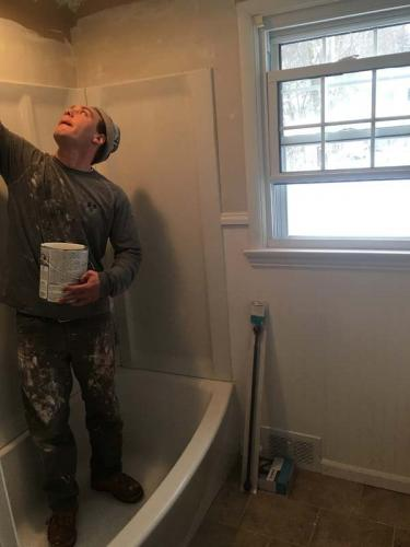 A Braendel Services team member works on installing a tub and shower in Erie, PA.