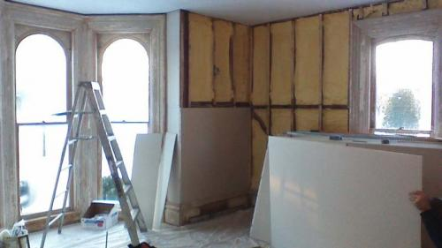 A shot of a room with bay windows. Drywall is ready to be hung!