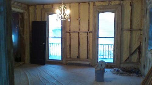 Looking inside a room with a door and two windows. The room is gutted, ready to be remodeled by the Braendel team.