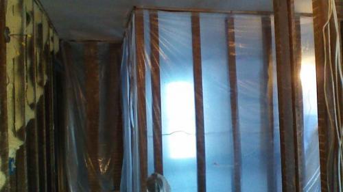 Tarping the framework of a wall during an interior renovation.