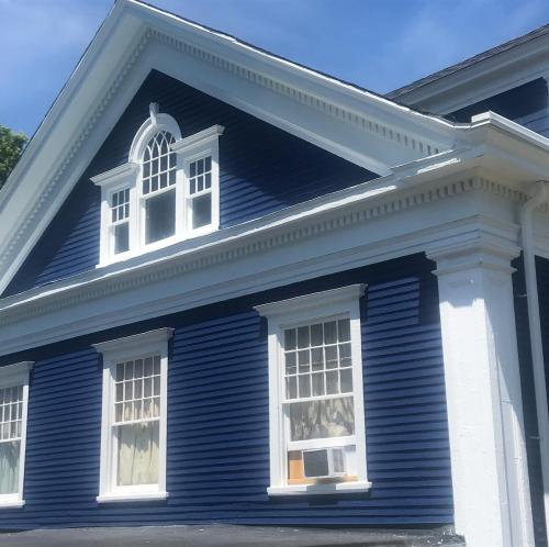 This deep blue siding and fresh trim make this house memorable.